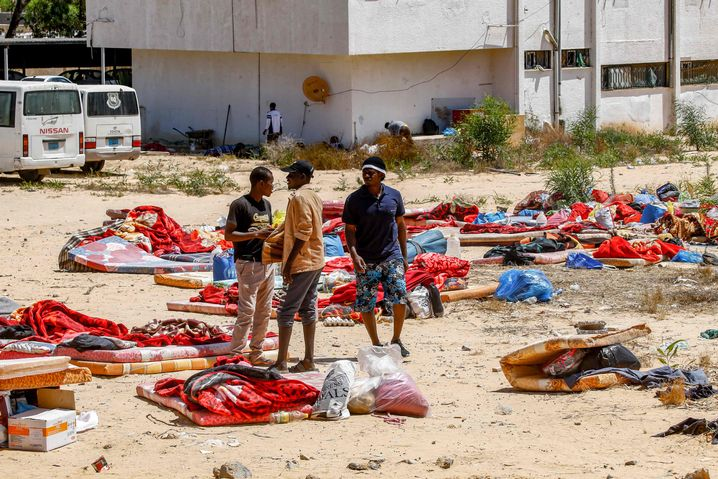 Migranten in den Trümmern des bombardierten Camps in Tajoura: