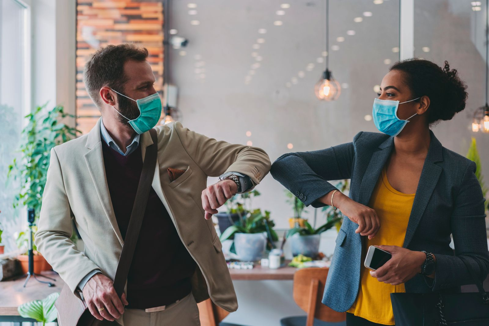 Business people greeting during COVID-19 pandemic, elbow bump