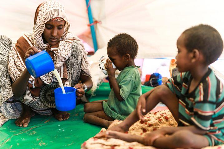 Eine Mutter in Äthiopien bereitet aus Milchpulver eine Mahlzeit für ihre Kinder zu, das Dorf ist auf Lebensmittelhilfen angewiesen