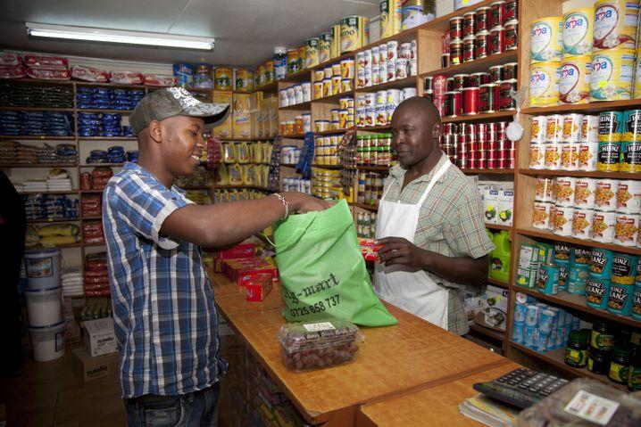 In Nairobi packt ein Mann seinen Einkauf in eine Stofftüte