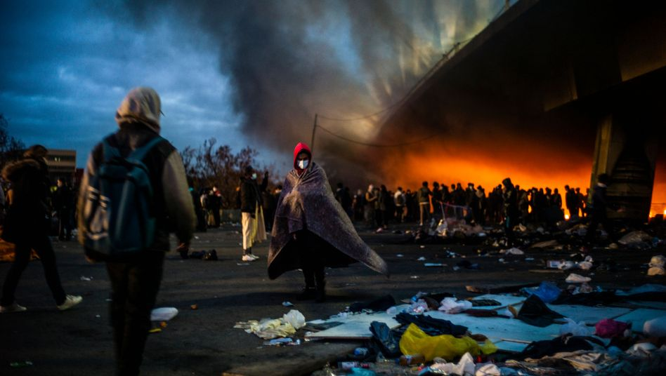 Feuer lodert am Morgen des 17. November unter der Autobahnbrücke in Saint-Denis. Viele der Bewohner wärmen sich an den Flammen, während sie auf ihre Evakuierung aus dem Camp warten