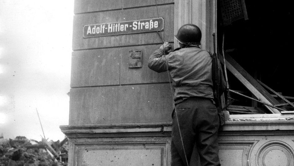 """""""Adolf-Hitler-Straße"""" in Düren: Amerikanischer Soldat entfernt Straßenschild im Februar 1945"""