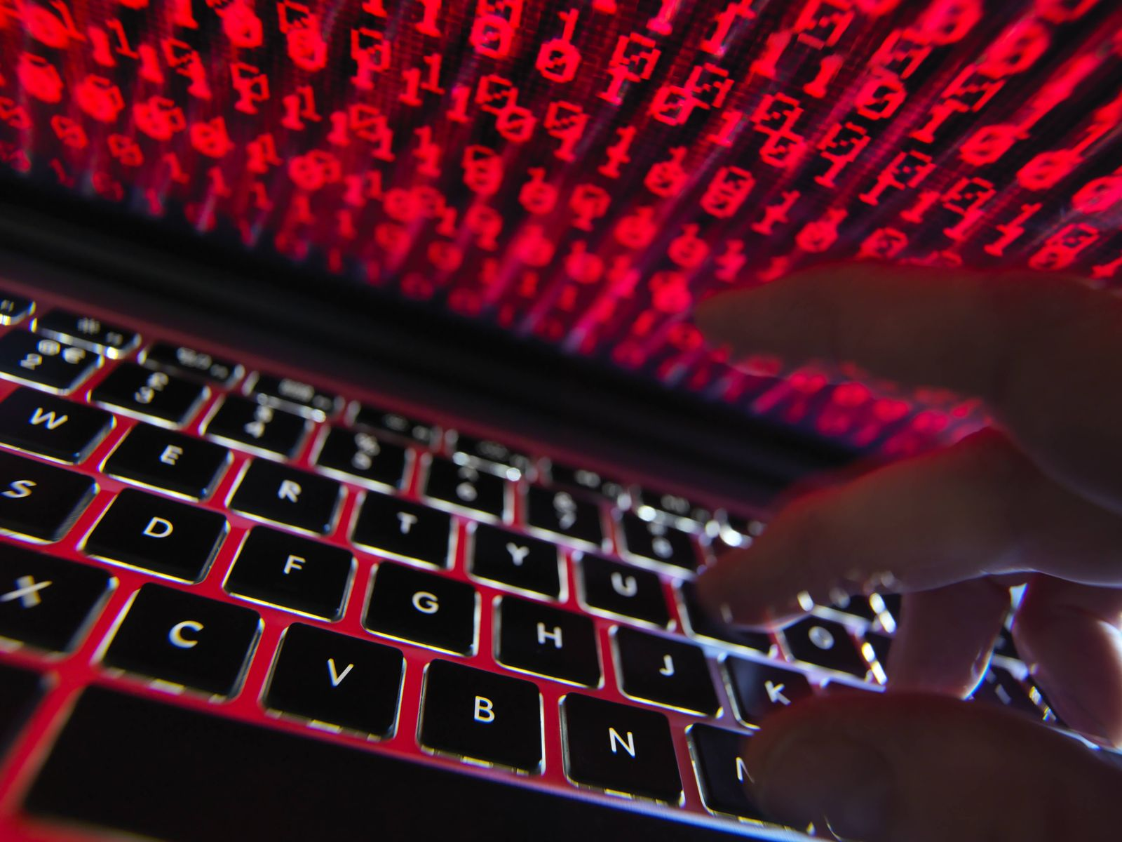 Hacker coding a computer virus infecting a laptop model released Symbolfoto property released PUBLI