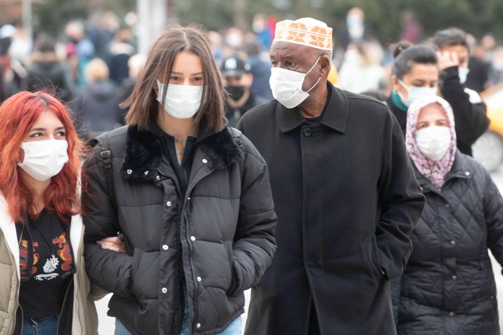 People wearing face masks walk on a street in Ankara, Turkey, on March 31, 2021. Turkey has confirmed 31,537 deaths and