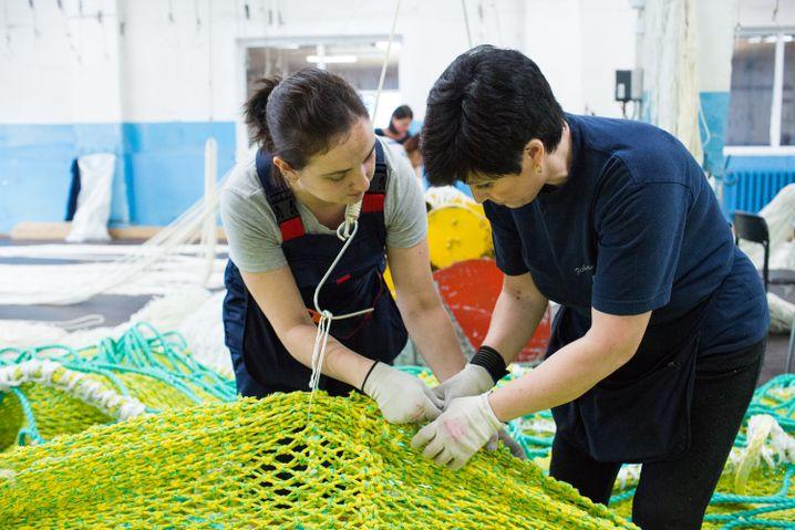Die Netzteile hängen an Haken kurz über der Erde, damit sich die Arbeiterinnen nicht immer bücken müssen
