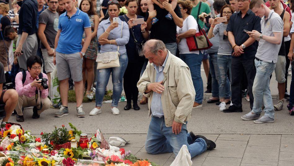Trauernde Menschen vor dem OEZ in München