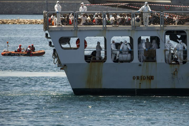 An Italian navy vessel carries migrants rescued on by the ship Acquarius after Italy refused to let them come ashore in the country.