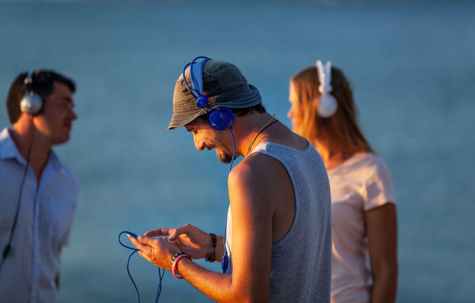 EINMALIGE VERWENDUNG 3 junge Menschen Kopfhörer