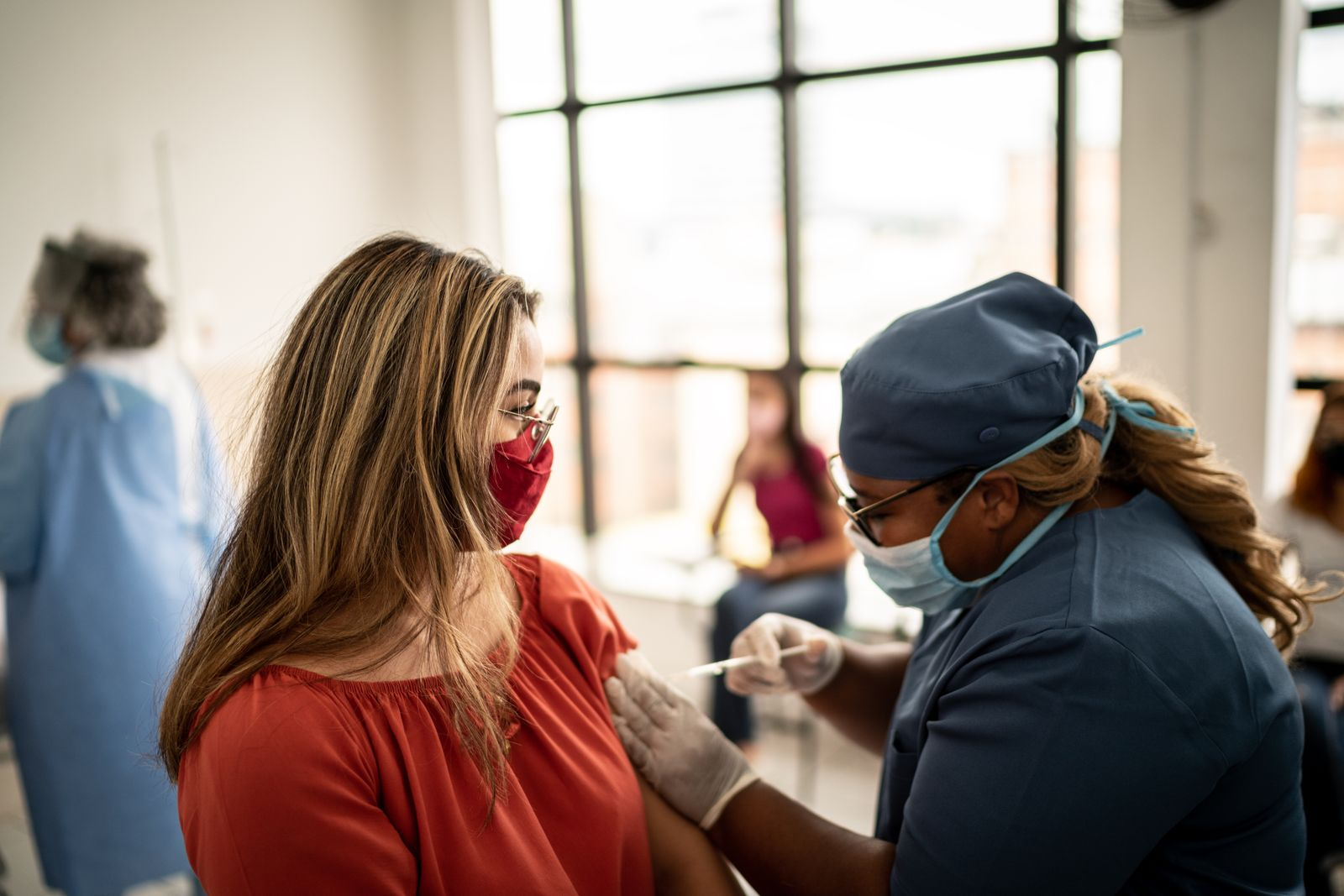 Teenager girl being vaccinated - wearing face mask