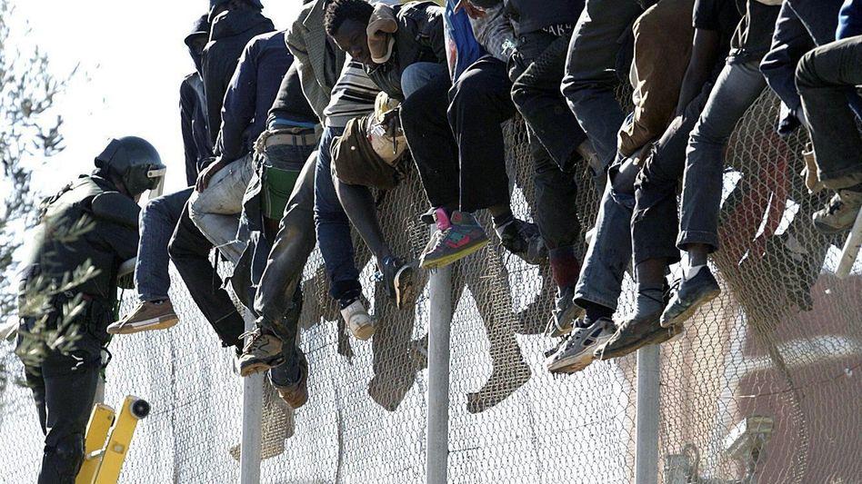 Menschen klettern über Grenzzaun zwischen Marokko und Melilla