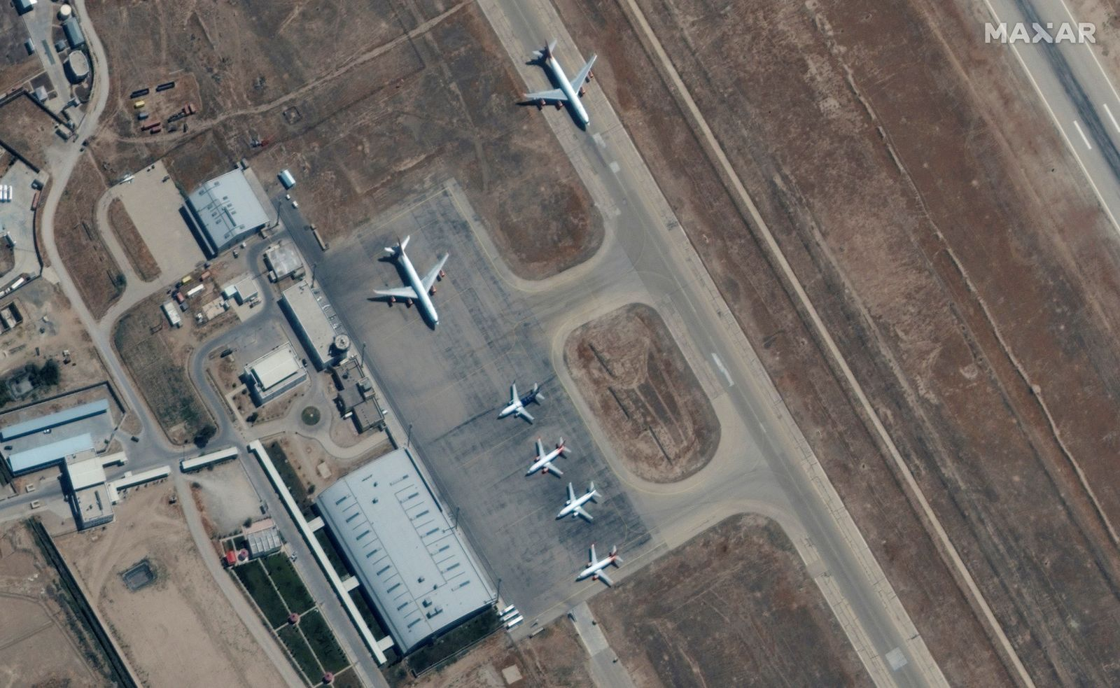 Six commercial airplanes are seen near the main terminal of the Mazar-i-Sharif airport