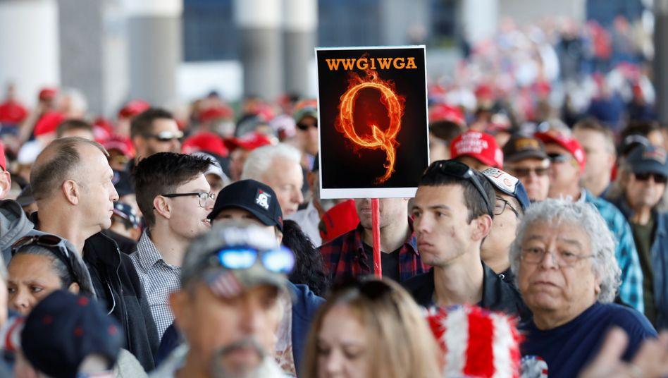 A QAnon supporter holds up a sign at a Trump rally.