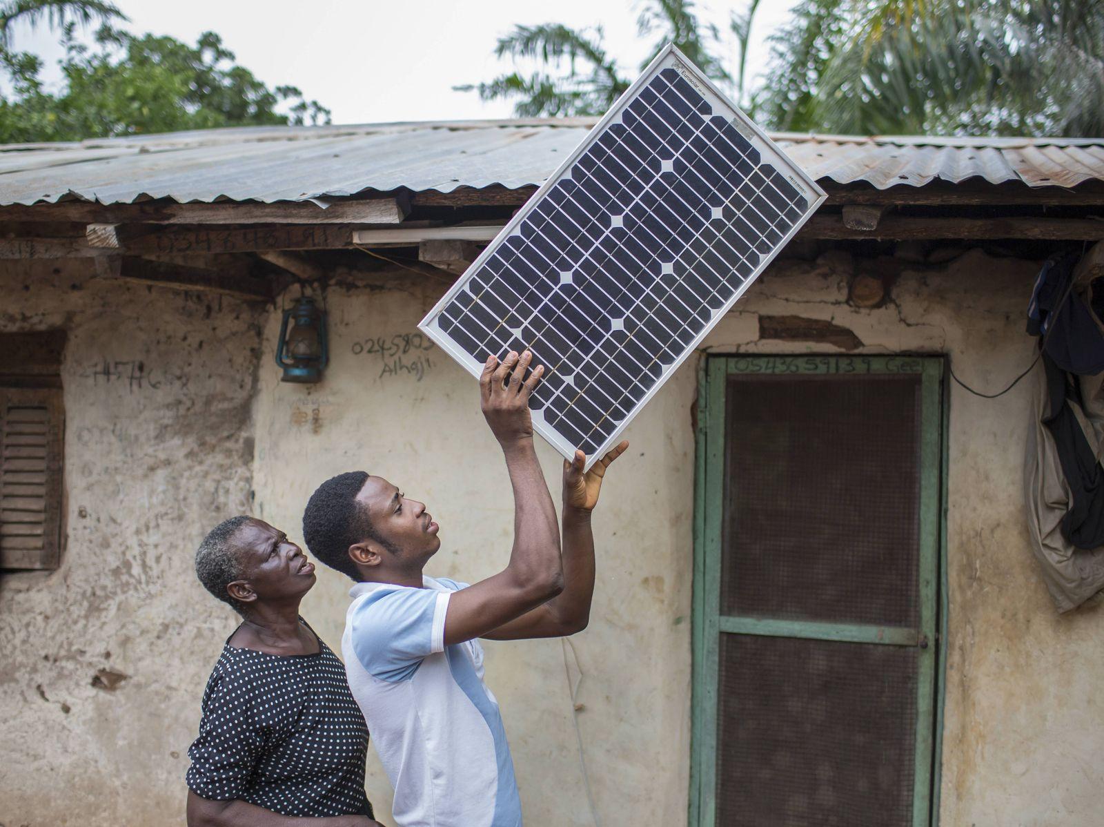 Ein junger afrikanischer Bauer legt ein Solarpanel auf das Dach seines Hauses auf einer Cashew Farm