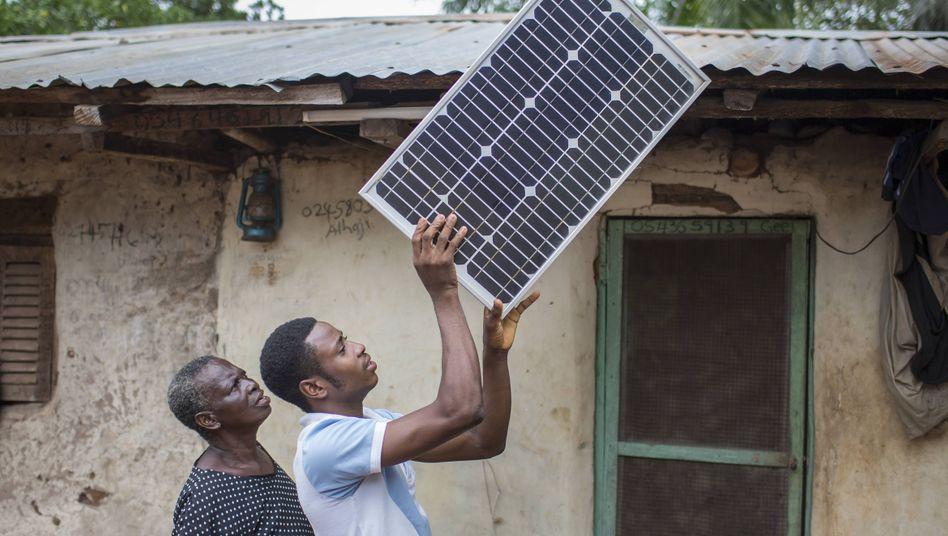 Dezentrale Stromversorgung: Einghanaischer Bauer legt ein Solarpanel auf das Dach seines Hauses