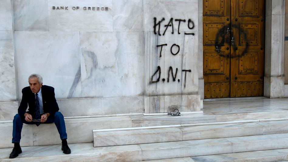 """A man sitting outside the Bank of Greece next to graffiti reading """"IMF Out."""" On Sunday, European finance ministers agreed to a bail-out package for the country."""