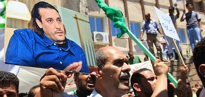 Libyans holding posters of Hannibal Gadhafi protest in front of Switzerland's embassy in Tripoli last Thursday.