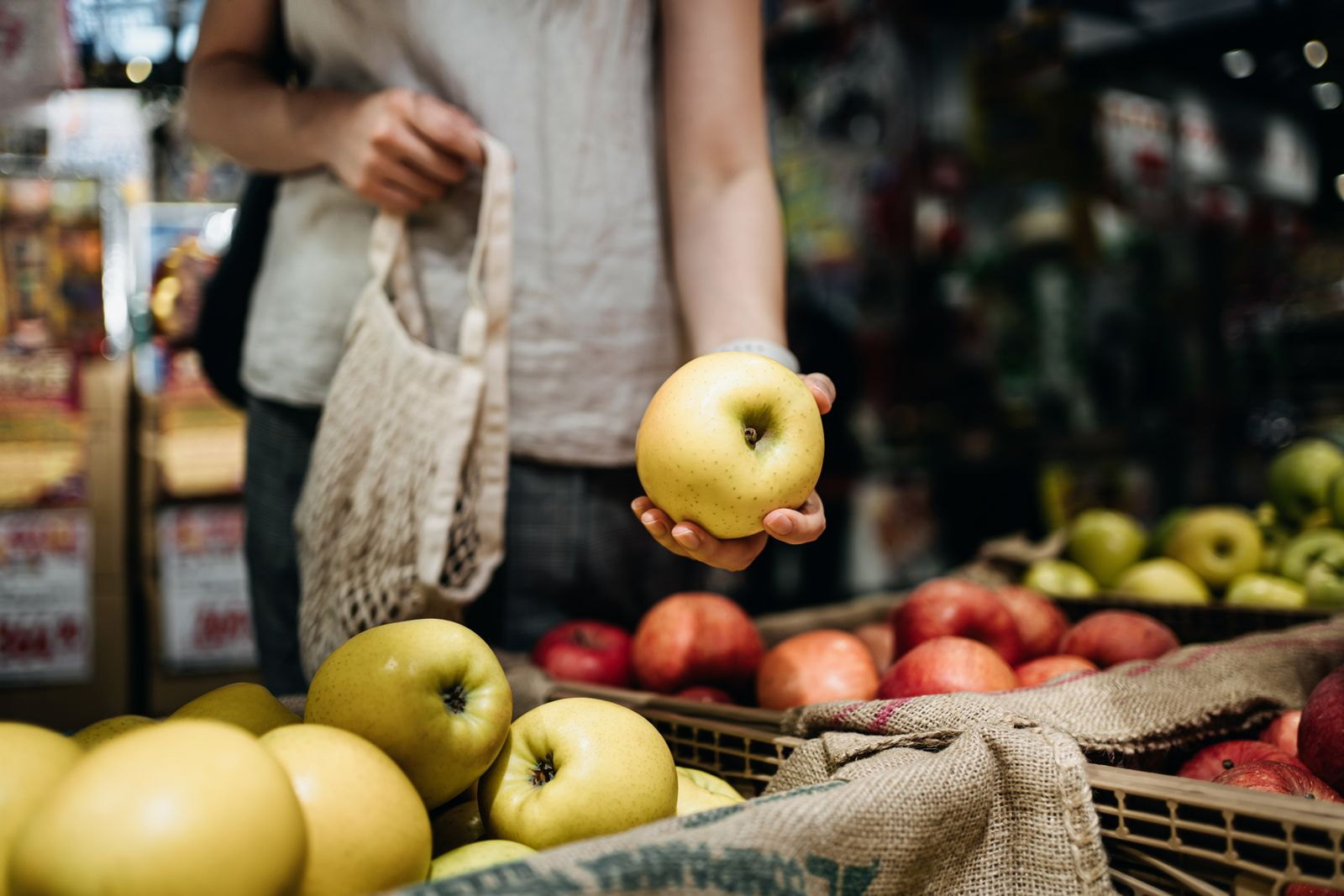 Close up of young Asian woman shopping for fresh organic fruits in farmer's market with a cotton mesh eco bag. Environmentally friendly and zero waste concept
