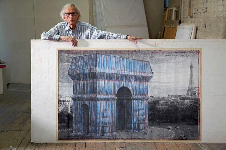 Christo mit einer Zeichnung des verhüllten Triumphbogenprojekts in seinem Atelier in Tribeca, New York 2019