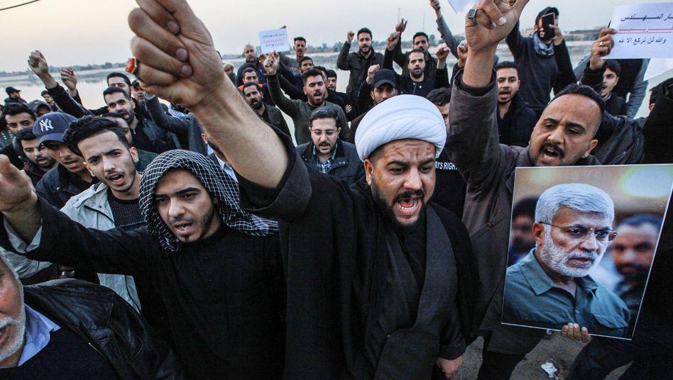 """Menschen in Bagdad protestieren gegen einen US-Luftangriff in Irak, bei dem unter anderem der iranische General Soleimani und """"Volksmobilisierungseinheiten""""-Vizechef Muhandis (auf dem Poster rechts) getötet wurden"""