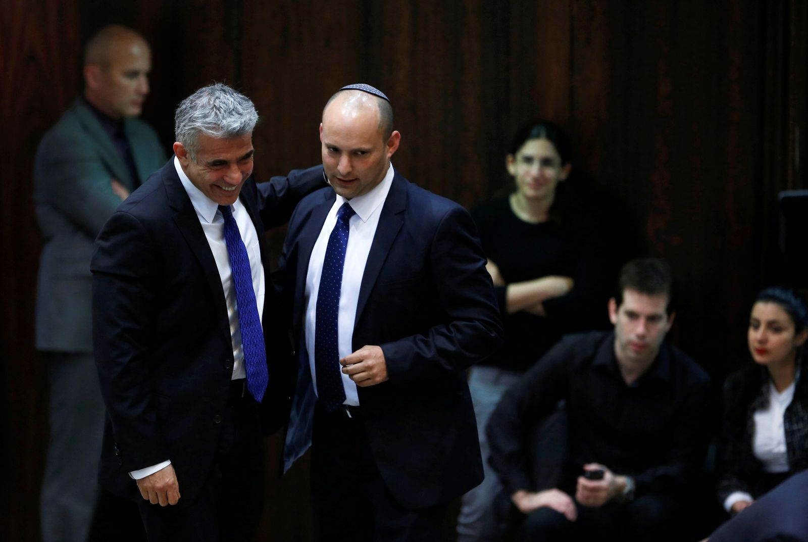 FILE PHOTO: Israel's Finance Minister Lapid and Minister of Economics and Trade Bennett walk together during the swearing-in ceremony at the Israeli Parliament, in Jerusalem