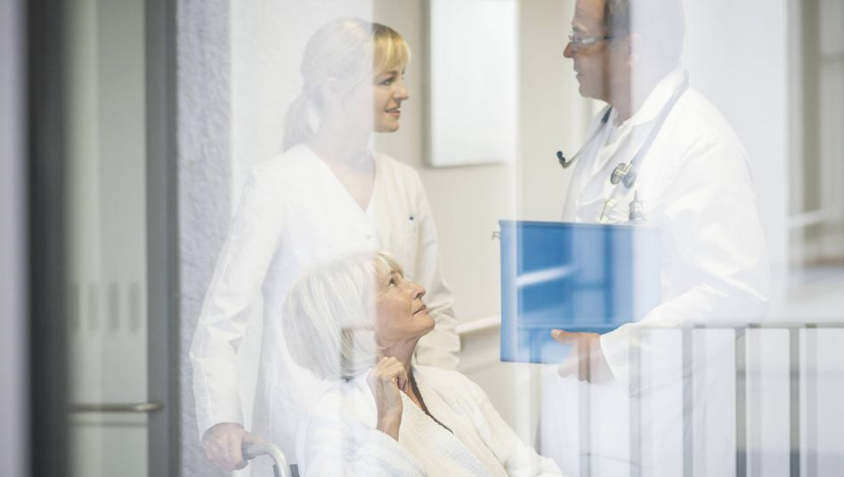 Pfleger und Arzt im Gespräch (Symbolbild)