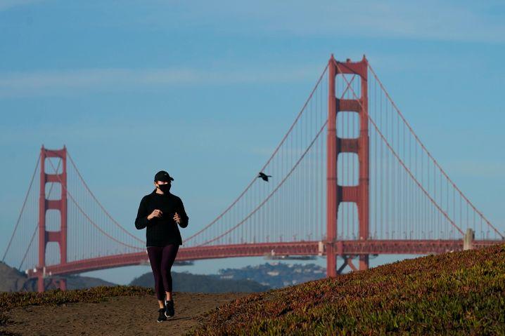 Eine Frau mitMund-Nasen-Schutz läuft auf einem Weg vor der Golden Gate Bridge