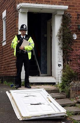 Ein Polizist steht vor der aufgebrochenen Tür eines der durchsuchten Häuser in Birmingham