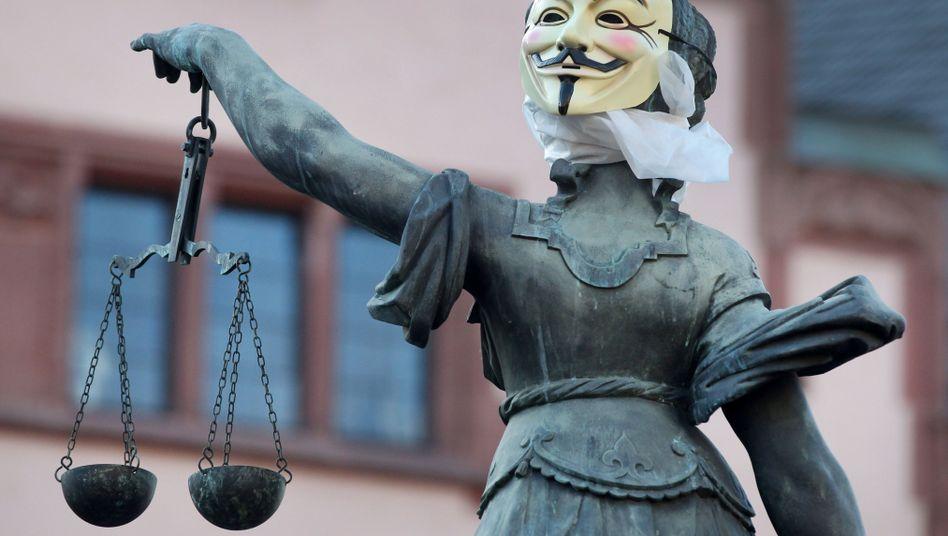 Justitia mit Anonymous-Maske (Archivbild): Gerichte stellen sich gegen Automatismus bei Filesharing-Verfahren