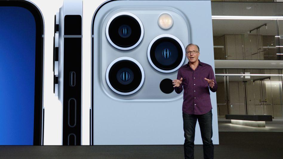 Marketingchef Greg Joswiak vor einem Foto des iPhone 13 Pro, das vor Apples Firmensitz projiziert wird