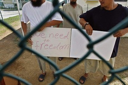 Uighur detainees at Guantanamo show a protest sign to the media in this June 1 photo.