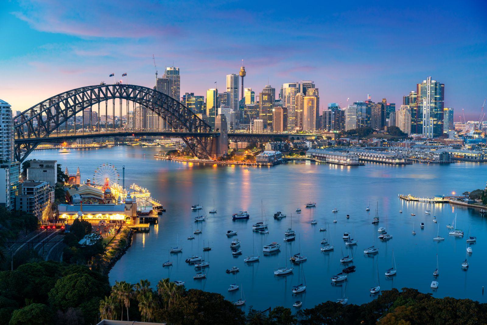 Cityscape image of Sydney, Australia with Harbor Bridge and Sydney skyline during sunset. Vacation and travel in Australia.