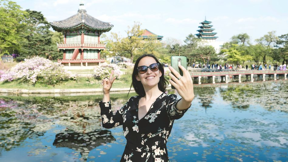 Eine Südkoreanerin fotografiert sich mit dem Smartphone (Symbolfoto)
