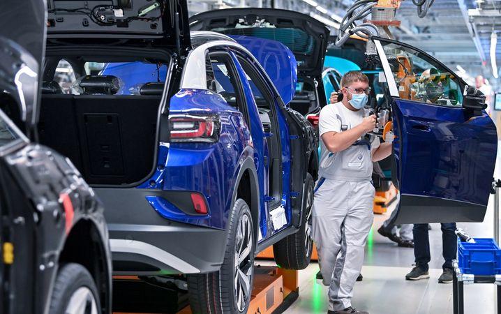 Ein Mitarbeiter im Volkswagenwerk in Zwickau komplettiert einen VW
