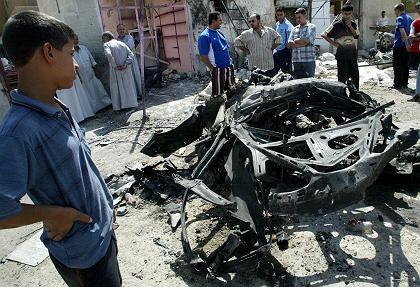 Bagdad: Anwohner umringen das Wrack des Autos in dem sich ein Selbstmordattentäter in die Luft gesprengt hat