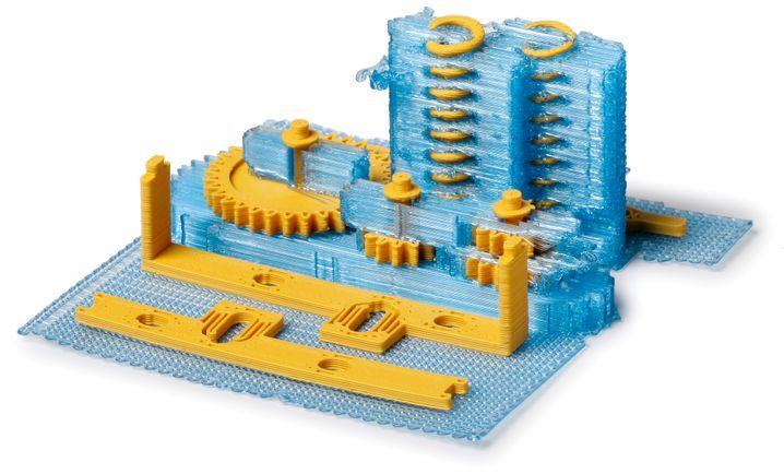 Stützstrukturen aus blauem PLA halten hier die Getriebeteile und Spiralfedern aus ockerfarbenem ABS in Form.
