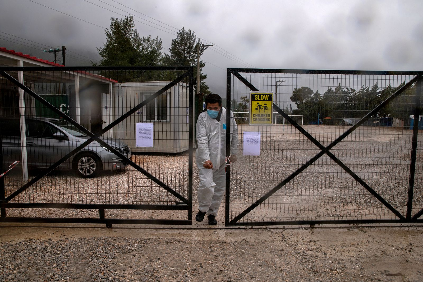 FILE PHOTO: A man wearing a protective suit and a face mask exits the Malakasa migrant camp after authorities found a coronavirus case and placed the camp under quarantine