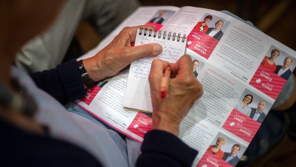Ein SPD-Mitglied macht sich während der Regionalkonferenz in Hannover Notizen über Bewerber