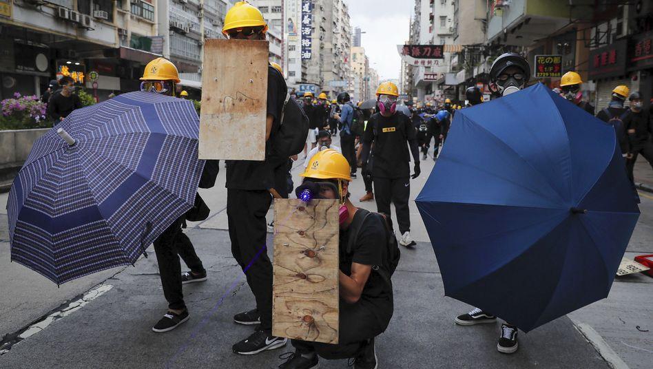 Demonstranten in Hongkong schützen sich mit Gasmasken, Regenschirmen und Holzschildern vor Tränengas bei Unruhen mit Polizisten auf einer Straße
