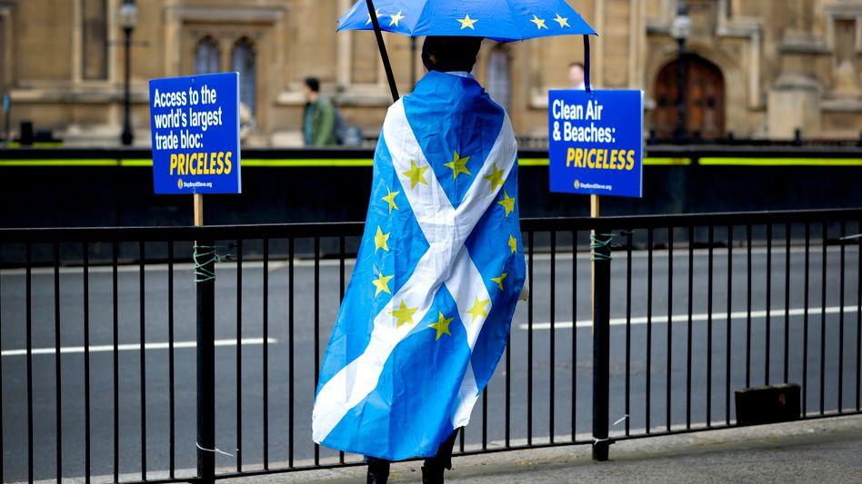 Symbolträchtig: Schottischer Anti-Brexit-Demonstrant unter EU-Schirm, gehüllt in eine Schottlandfahne mit EU-Sternen