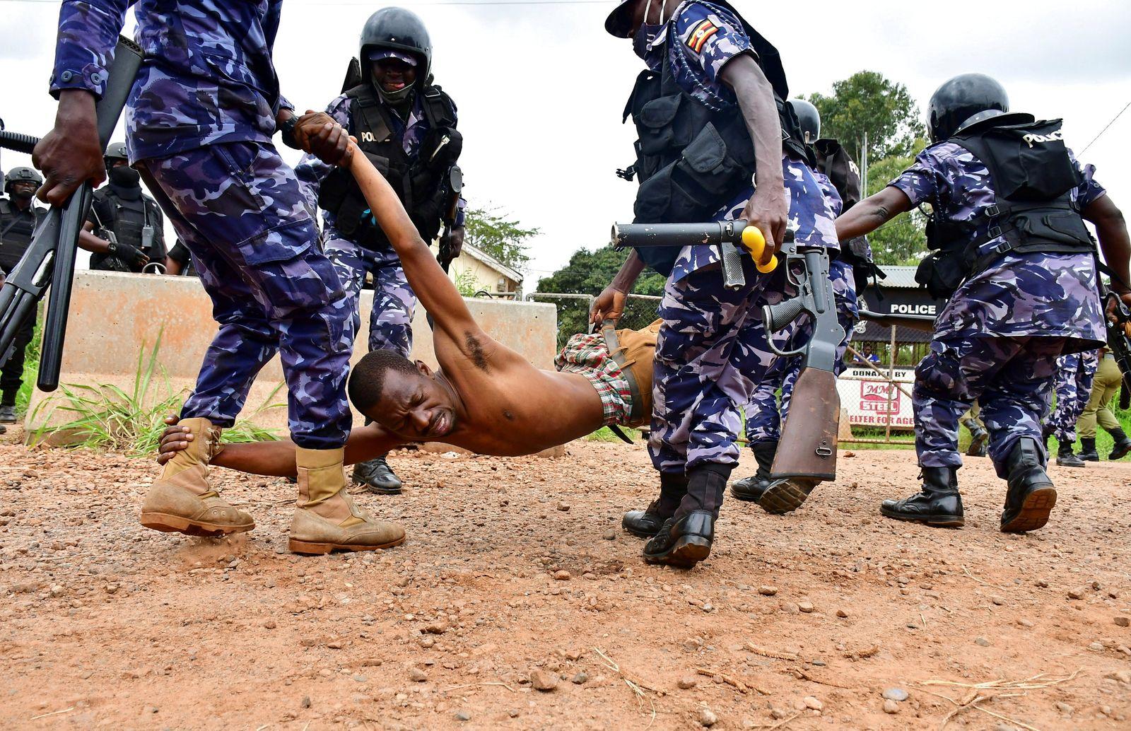 Ugandan riot policemen detain a supporter of presidential candidate Robert Kyagulanyi, in Luuka district