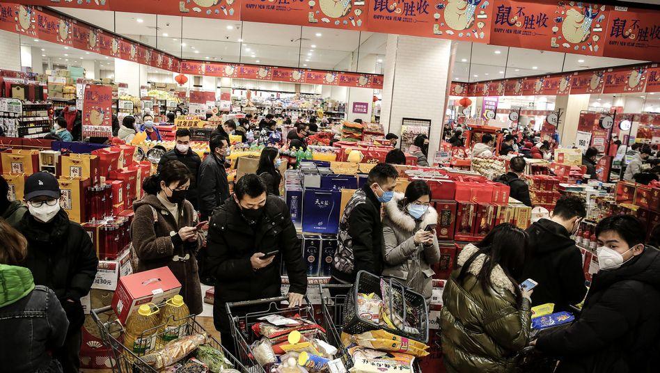 Kunden eines Supermarkts in der chinesischen Metropole Wuhan schützen sich mit Masken vor einer möglichen Infektion mit dem Coronavirus