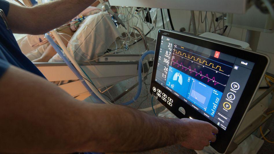 Ein Arzt bedient eine Beatmungsmaschine auf einer Intensivstation