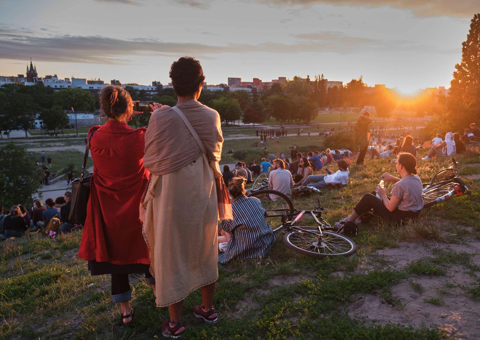 Abendsonne Deutschland, Berlin, 21.206.2020, Mauerpark, zwei Frauen, Handyfoto, Besucher auf der Wiese, Sonnenuntergang,