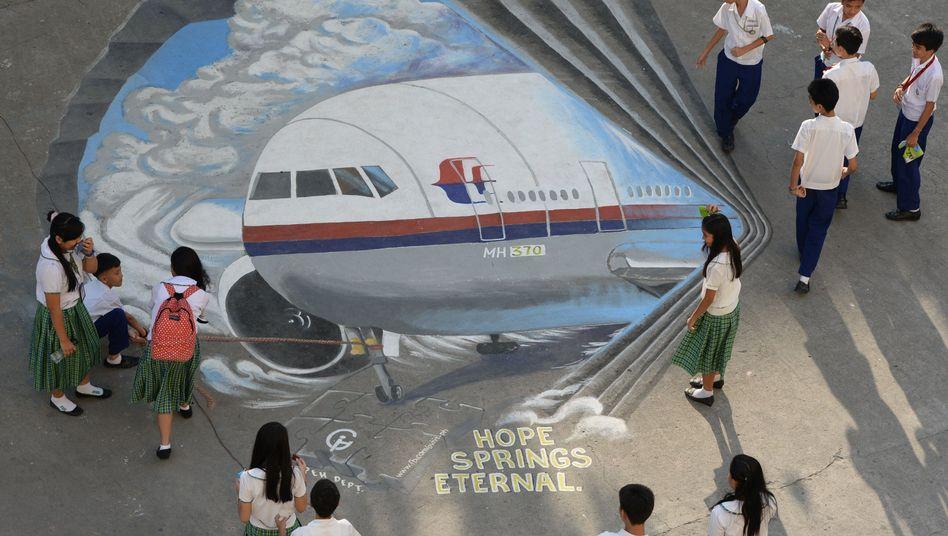 Schulkinder in Manila schauen auf eine Kreidezeichnung der Boeing: Seit zwölf Tagen keine Spur