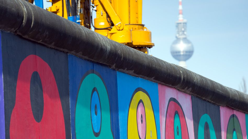A piece of construction machinery next to the East Side Gallery, the longest-surviving stretch of the Berlin Wall.