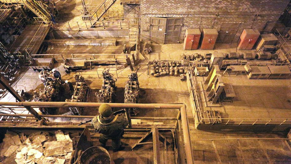 A pro-Russian rebel guards as workers work at the Uzov Metallurgical Works in Donetsk.