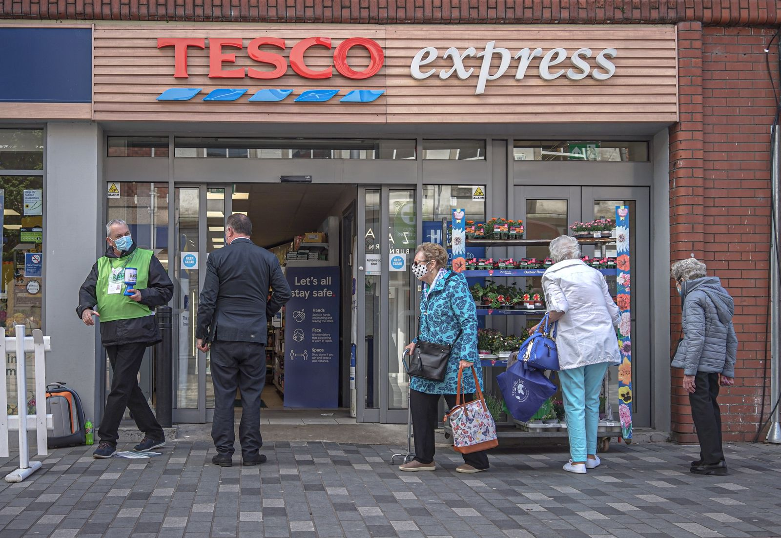 Customers enter Tesco Express on Bow St