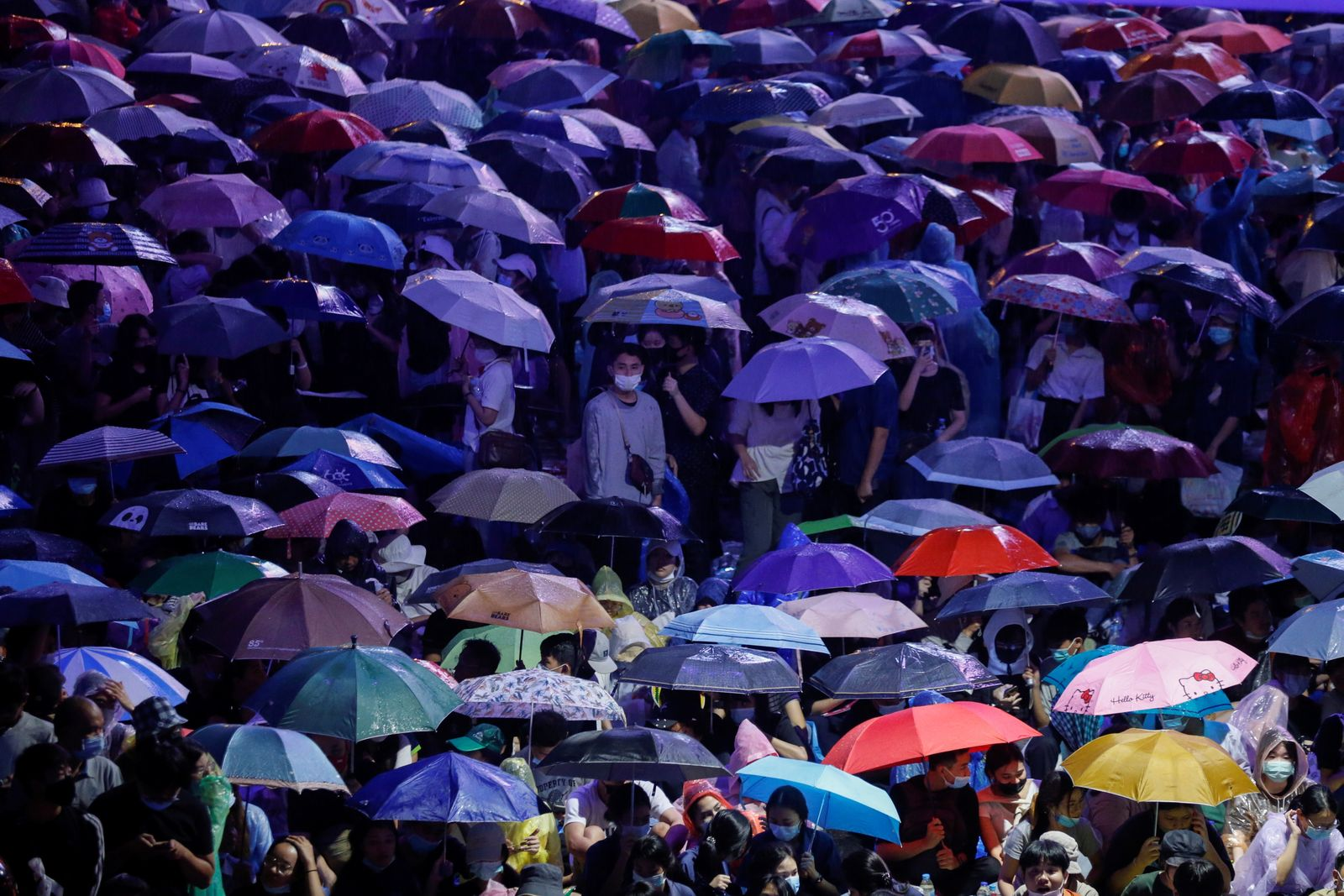 People cover themselves with umbrellas during anti-government protests, in Bangkok