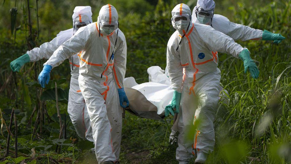 Ein verstorbener Ebola-Patient wird im Kongo von Gesundheitsspezialisten getragen