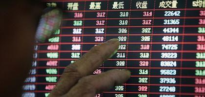 """Börseninteressierter vor Kurstafel (in Shanghai): """"Viele Aktien sind so billig wie seit einem Vierteljahrhundert nicht mehr"""""""